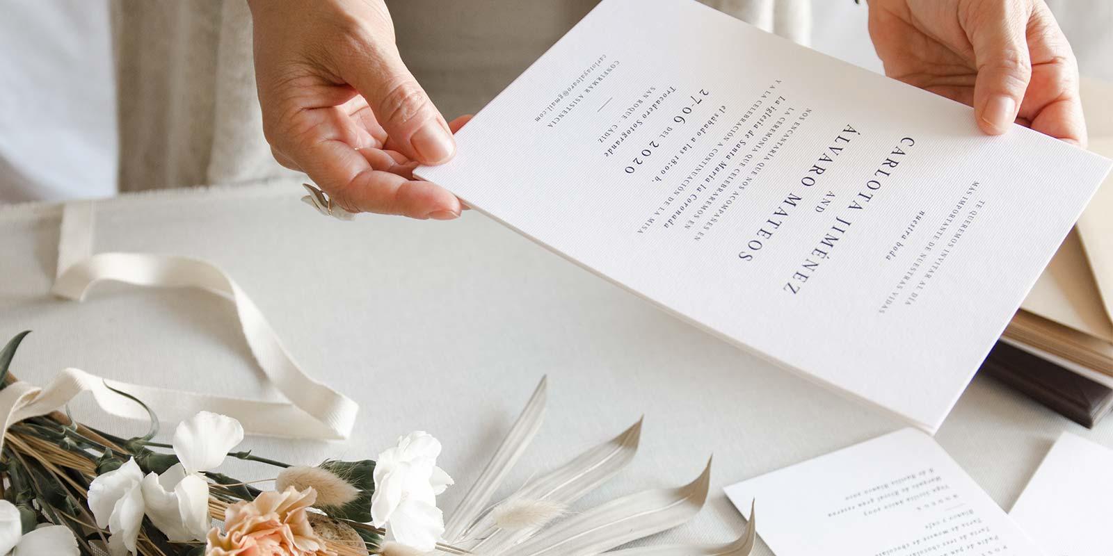 manos sujetando invitacion de boda blanca