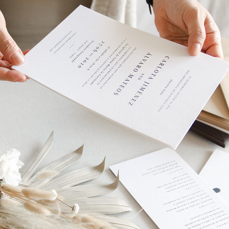 manos sujetando invitacion de boda minimalista
